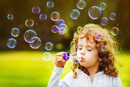 little girl blowing soap bubbles in summer park. Background toninf for instagram filter.