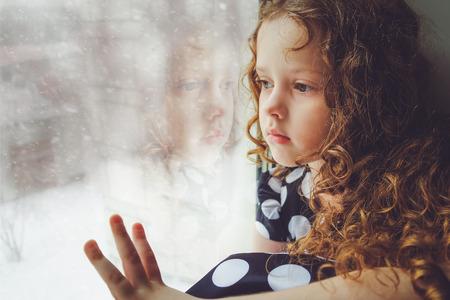Bambino triste guardando fuori dalla finestra sulla neve che cade. Tonificante foto. Archivio Fotografico