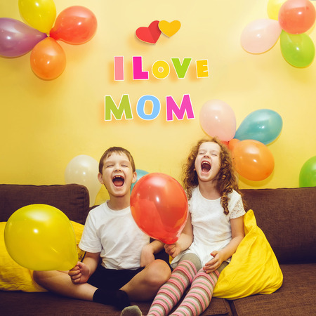 congratulate: Happy laughing children congratulate his mother with a holiday. Happy Mothers Day concept.