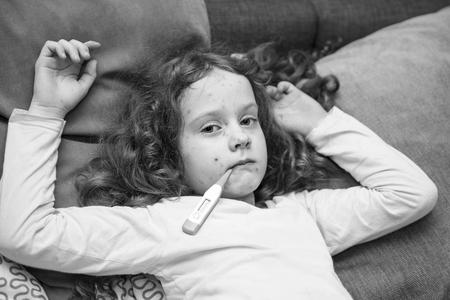 varicella: Child measuring temperature. Varicella zoster virus or Chickenpox. Black and white portrait.