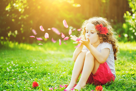 Little girl blowing flower petals from her hands in the sunlight.