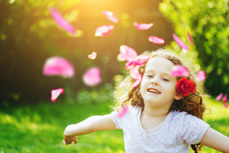 Free happy child in park enjoying nature. Girl hand up with flying flower petals in the air. Happy childhood and freedom concept. Imagens