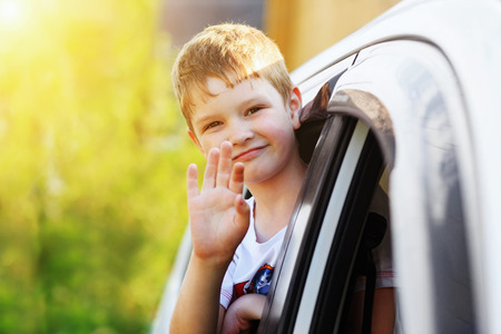 leaned: Child leaned out the window of a car and waving his hand.