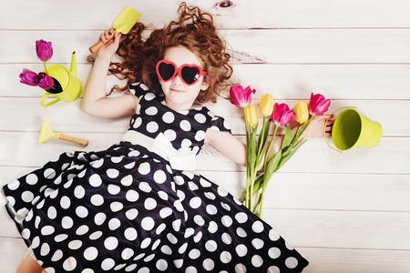 白の木製の床に横になっているチューリップの花束と巻き毛の女の子。春の背景、誕生日パーティー、健康的なライフ スタイル、バレンタインの日