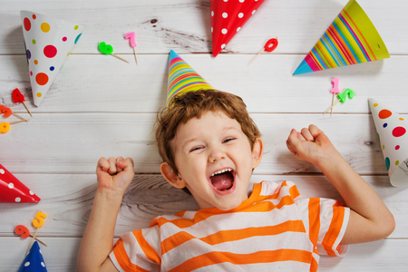Laughing baby lying on the wooden floor with festive caps and candles on a birthday party. Healthy smiling, Happy childhood concept.