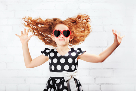 curly: Jumping little girl with flying hair in a fashionable dress. Stock Photo
