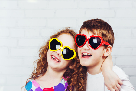 toothless: Embracing boy and girl with sunglassec heart shape.  Happy toothless smiling friend.