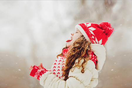 catches: Funny girl stuck out her tongue and catches snowflakes. Happy childhood. Traveling. Christmas concept.