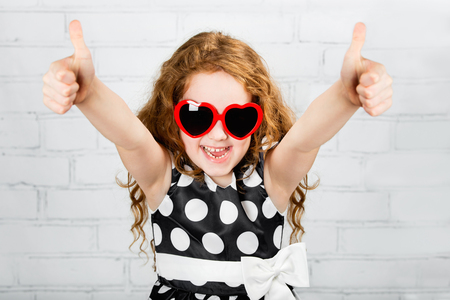 Laughing girl with sunglasses in heart shape, showing thumbs up. Stock Photo