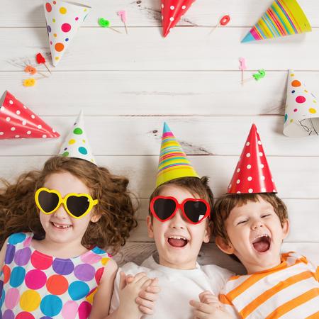 niños riendose: amigo niño feliz en la fiesta de carnaval, acostado en un piso de madera. concepto de infancia feliz. vista superior de alta Foto de archivo