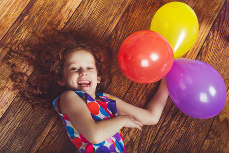 Laughing little girl in birthday party lying on wooden floor. Happy childhood concept.