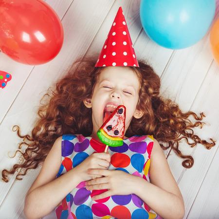 girl licking: Sweet little girl licking a lollipop.