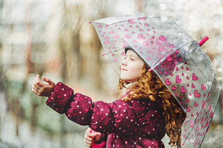 Little girl stretches her hand to catch falling raindrop. First spring or autumn rain.