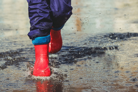 Child with red boots is jumping into a puddle in raining spring or autumn outdoor. Stock Photo