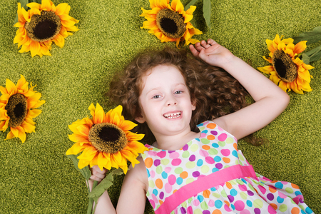 carpet grass: Curly girl with sunflower in grass carpet. Stock Photo