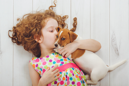 baby animal: Little girl and her puppy whispers on wood background.