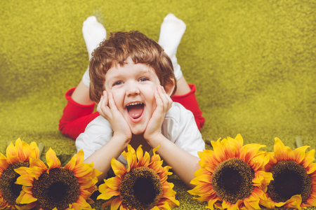 Cute child with sunflower lying on the green carpet. Stock Photo