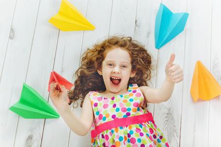 infancia: Riendo niña de lanzar avión de papel en el interior y, mostrando los pulgares arriba. infancia feliz, los viajes, el concepto de vacaciones. Vista superior.