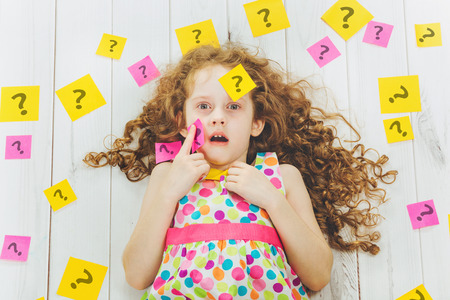 Smart child with question symbol on stickers on his body and around. Stress from studying, homework. Education concept. Foto de archivo