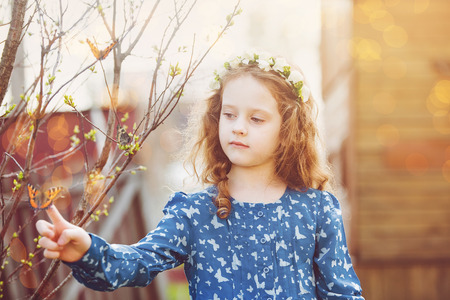 animal angelic: Spring little girl with a butterfly on his finger. Happy childhood concept. Stock Photo