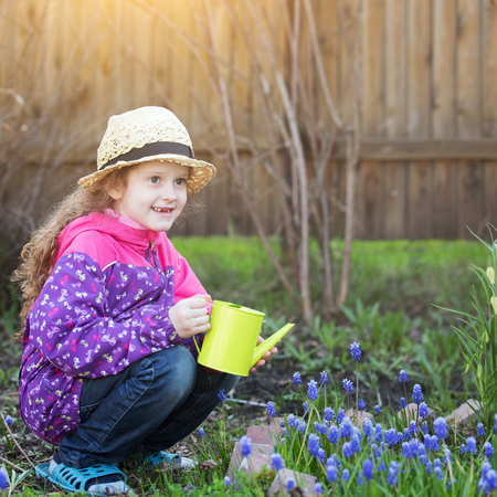 Child watering a plant with watering can. Stock Photo