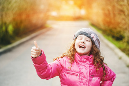good looks: Laughing girl showing thumbs up. Stock Photo