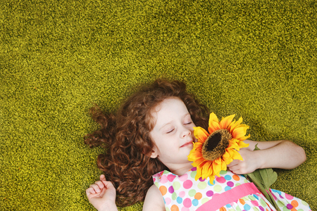 green carpet: Cute child with sunflower sleeping on the green carpet.