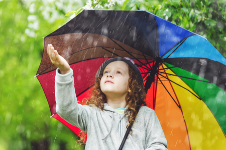 Curly child enjoy to spring rain outdoors.