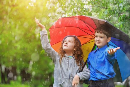 Children under umbrella enjoy to spring rain outdoors.