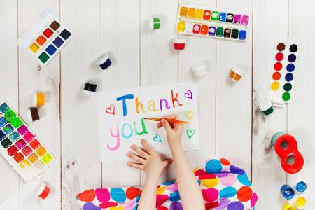 La main de l'enfant est en train d'écrire dans l'album mot «Merci». Thanksgiving carte de voeux. Banque d'images - 59219589