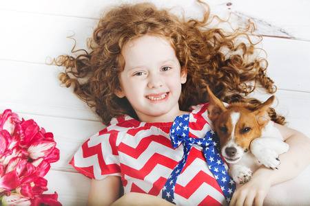 toothless: Family celebration 4th july. Independence Day concept. Laughing toothless girl hugging a puppy. Stock Photo