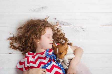 Cute girl étreindre un chiot et dormir sur le plancher en bois chaleureux.