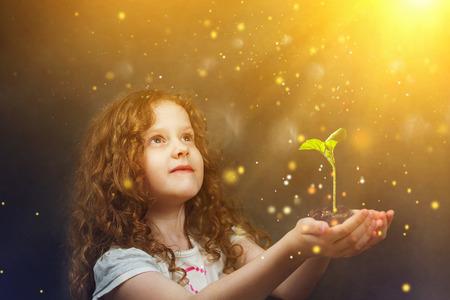 germinación: Niña que sostiene la planta joven verde en la luz del sol. Concepto de la ecología.