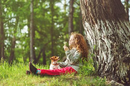 어린 소녀와 그녀의 강아지 민들레 비행을 즐길 수 있습니다. 큰 나무 아래 공원에서 쉬고 아이입니다. 스톡 콘텐츠