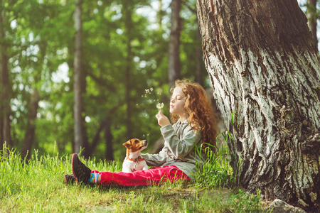 summer nature: Little girl and her puppy enjoy flying dandelions. Child resting in a park under a large tree. Stock Photo