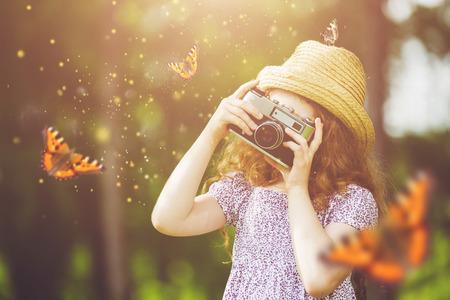 Niña en el sombrero de paja, vestido de estilo rústico, mariposa fotografía con la cámara de fotos retro en el bosque de cuento de hadas.