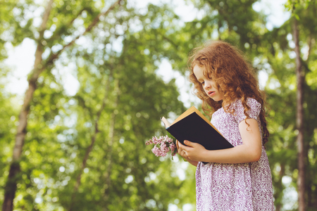 person reading: Little Girl hold bouquet of lilacs and reading the book in spring park . Retro portrait cute child in Little Girl hold bouquet of lilacs and reading the book in spring park . Retro portrait cute child in country style.
