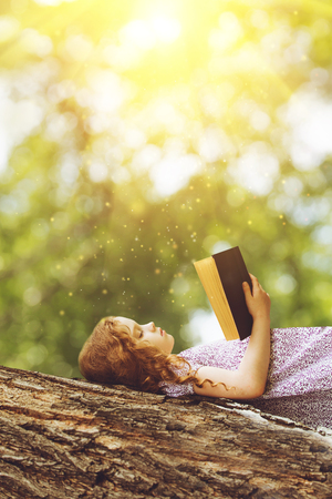 Serious little girl reading the Bible or a book on a big tree in the rays of sunset.