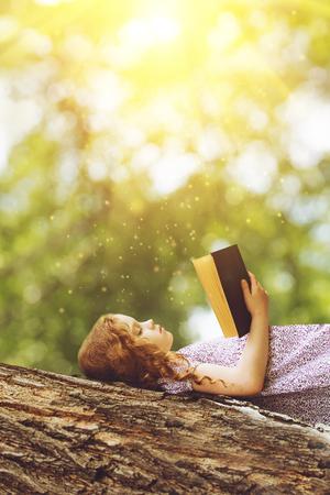 Ernstes kleines Mädchen, die Bibel oder ein Buch auf einem großen Baum in den Strahlen der Sonne zu lesen.