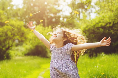Child outstretched arms enjoying flying yellow dandelion in sunset light. filter. Healthcare, medical concept.