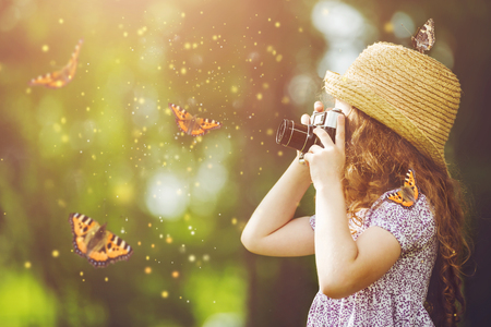 photographers: Little girl in straw hat, rustic style dress, photographing butterfly with retro photo camera in fairytale forest.
