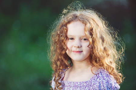 Summer portrait of a smiling golden-haired girl in the park, background toning for filter.