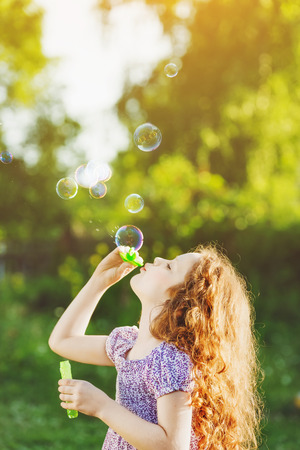girl blowing: little girl blowing soap bubbles Stock Photo