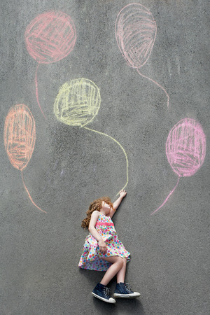 dreamy: Dreamy little girl l flying with painted balloons. Happy childhood concept.
