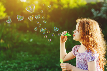 Princess girl blowing soap bubbles with heart shaped, happy childhood concept. Standard-Bild