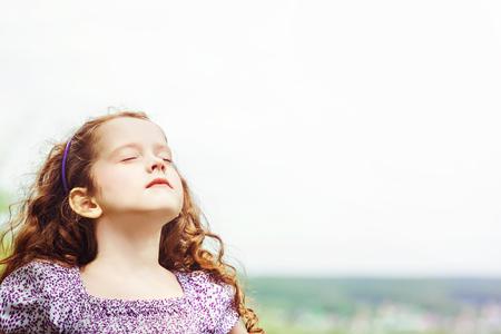 어린 소녀는 그녀의 눈을 폐쇄하고 신선한 공기 야외 숨을 쉰다.