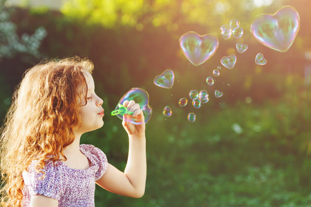 Princess girl blowing soap bubbles with heart shaped, happy childhood concept. Imagens