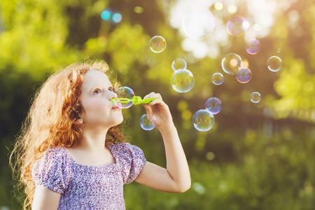 bulles de savon: petite fille soufflant des bulles de savon dans le parc de l'été. toninf d'arrière-plan pour le filtre.