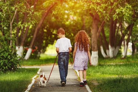Child friend and puppy walking to the summer park. Standard-Bild
