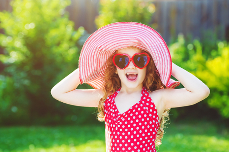 holyday: Laughing girl in red swimsuit, big hat and sunglasses heart, have a funny summer holyday. Stock Photo